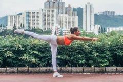Actitud de equilibrio horizontal practicante profesional del palillo de la yoga del atleta de sexo femenino que se coloca en una  Imagenes de archivo