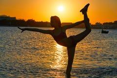 Actitud de la gimnasia de la muchacha en la playa de la puesta del sol imagenes de archivo