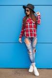 Actitud de la muchacha del inconformista de la moda en gafas de sol y sombrero en la pared azul outdoor Imágenes de archivo libres de regalías