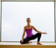 Actitud de la yoga adentro en alféizar Fotografía de archivo