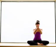 Actitud de la yoga adentro en alféizar Imagen de archivo libre de regalías