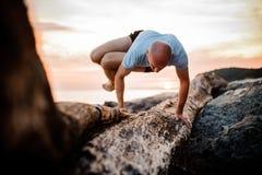 Actitud de la yoga de la posición del pino del hombre en la playa cerca del océano Fotos de archivo