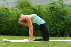 Actitud de la yoga del camello de la demostración de la mujer joven Foto de archivo libre de regalías