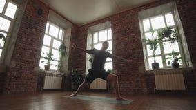Actitud de la yoga del guerrero de la práctica del hombre en estudio con la pared de ladrillo y las ventanas grandes almacen de metraje de vídeo