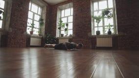 Actitud de la yoga de la práctica del hombre en estudio con la pared de ladrillo Concepto sano de la forma de vida metrajes