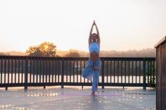 Actitud de Vrikshasana La mujer joven está haciendo yoga en la salida del sol fotos de archivo