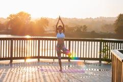 Actitud de Vrikshasana La mujer joven está haciendo yoga en la salida del sol foto de archivo