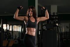 Actitud del bíceps de una mujer joven en gimnasio Foto de archivo libre de regalías