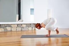 Actitud del cuervo de la yoga en gimnasio de madera del piso Imágenes de archivo libres de regalías