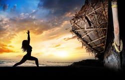 Actitud del guerrero de la silueta de la yoga cerca del barco Imágenes de archivo libres de regalías