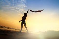 Actitud del juego de la mujer de la forma de vida de la silueta en puesta del sol de la playa Imagen de archivo libre de regalías