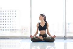 Actitud del loto de la meditación Yoga practicante de la mujer atractiva joven, sentándose en ejercicio, resolviéndose, ropa de d Imágenes de archivo libres de regalías
