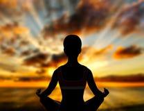 Actitud del loto de la yoga en la puesta del sol Fotos de archivo libres de regalías