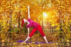 Actitud del trikonasana de la yoga de la Navidad Imagenes de archivo