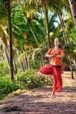 Actitud del vrikshasana de la yoga en bosque de la palma Foto de archivo libre de regalías