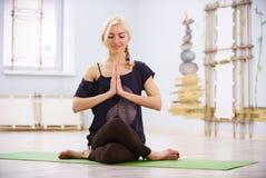 Actitud deportiva hermosa de Garudasana Eagle del asana de la yoga de las prácticas de la mujer de la yogui del ajuste en el cuar fotografía de archivo