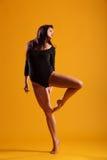 Actitud dramática de la danza de la mujer contra amarillo Foto de archivo