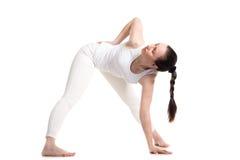 Actitud femenina del triángulo de la yoga de la yogui que hace Imágenes de archivo libres de regalías