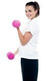 Actitud lateral de la muchacha con la elaboración de las pesas de gimnasia Foto de archivo