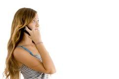 Actitud lateral de la mujer joven que habla en el teléfono celular Foto de archivo libre de regalías
