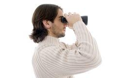 Actitud lateral del hombre joven que mira con binocular Imagen de archivo libre de regalías