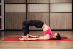 Actitud modelo femenina del puente de la yoga que hace en el gimnasio, el arco ascendente o la postura de la rueda Imagen de archivo