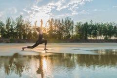 Actitud practicante de la yoga del guerrero de la mujer al aire libre foto de archivo libre de regalías