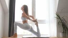 Actitud practicante de la yoga del guerrero de la mujer dentro contra fondo de la ventana almacen de metraje de vídeo