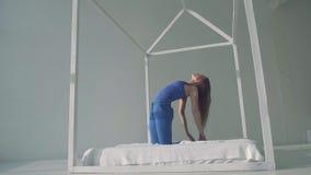 Actitud practicante del camello de la mujer hermosa de la yoga en cama almacen de video