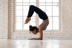 Actitud practicante del escorpión de la yoga de la mujer atractiva deportiva joven imágenes de archivo libres de regalías