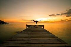 Actitud practicante del guerrero de la yoga de la silueta de la mujer a pie en el puente del mar en la puesta del sol Foto de archivo libre de regalías