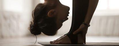 Actitud practicante del uttanasana de la mujer horizontal de la imagen que hace ejercicio delantero de la curva imagenes de archivo