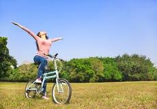 Actitud relajante de la mujer joven y el sentarse en la bici Fotos de archivo