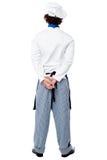 Actitud trasera de un cocinero de sexo masculino en uniforme imagen de archivo libre de regalías