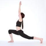 Actitud Virabhadrasana del guerrero uno de la yoga de la mujer del ajuste Foto de archivo libre de regalías