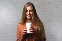 Actitudes alegres de la muchacha con una taza de café Fotografía de archivo