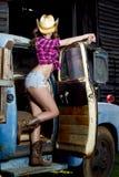Actitudes atractivas del cowgirl con el carro viejo Imagen de archivo libre de regalías