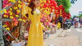 Actitudes de la chica joven por las flores en el Año Nuevo TET del mercado callejero almacen de metraje de vídeo