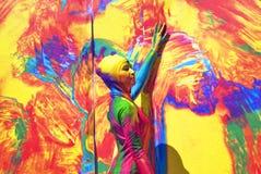 Actitudes de la mujer para los fotos en el fondo colorido