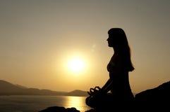 Actitudes de la yoga en la salida del sol Fotos de archivo