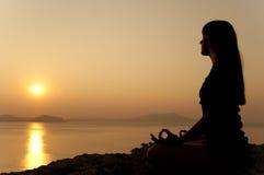 Actitudes de la yoga en la salida del sol Fotografía de archivo