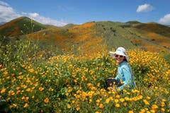 Actitudes de las gafas de sol de la mujer que llevan joven y del sombrero de paja en campo de la amapola en California fotografía de archivo libre de regalías