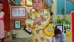 Actitudes de Little Boy del primer en la tienda de las decoraciones por el Año Nuevo TET almacen de metraje de vídeo