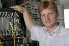 Actitudes del ingeniero de las telecomunicaciones en fondo del multiplexor Fotografía de archivo