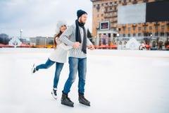 Actitudes felices de los pares del amor en pista de patinaje Imagen de archivo