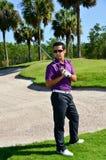 Actitudes masculinas del golfista con el club de golf Fotos de archivo