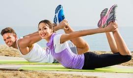Actitudes practicantes de la yoga del individuo y de la muchacha que se colocan en la playa Foto de archivo