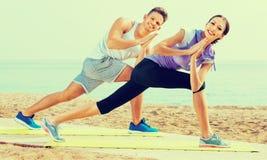 Actitudes practicantes de la yoga del individuo y de la muchacha que se colocan en la playa Foto de archivo libre de regalías
