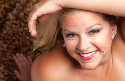 Actitudes rubias hermosas de la mujer en la manta del leopardo. Fotos de archivo
