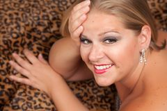 Actitudes rubias hermosas de la mujer en la manta del leopardo. Imagen de archivo libre de regalías